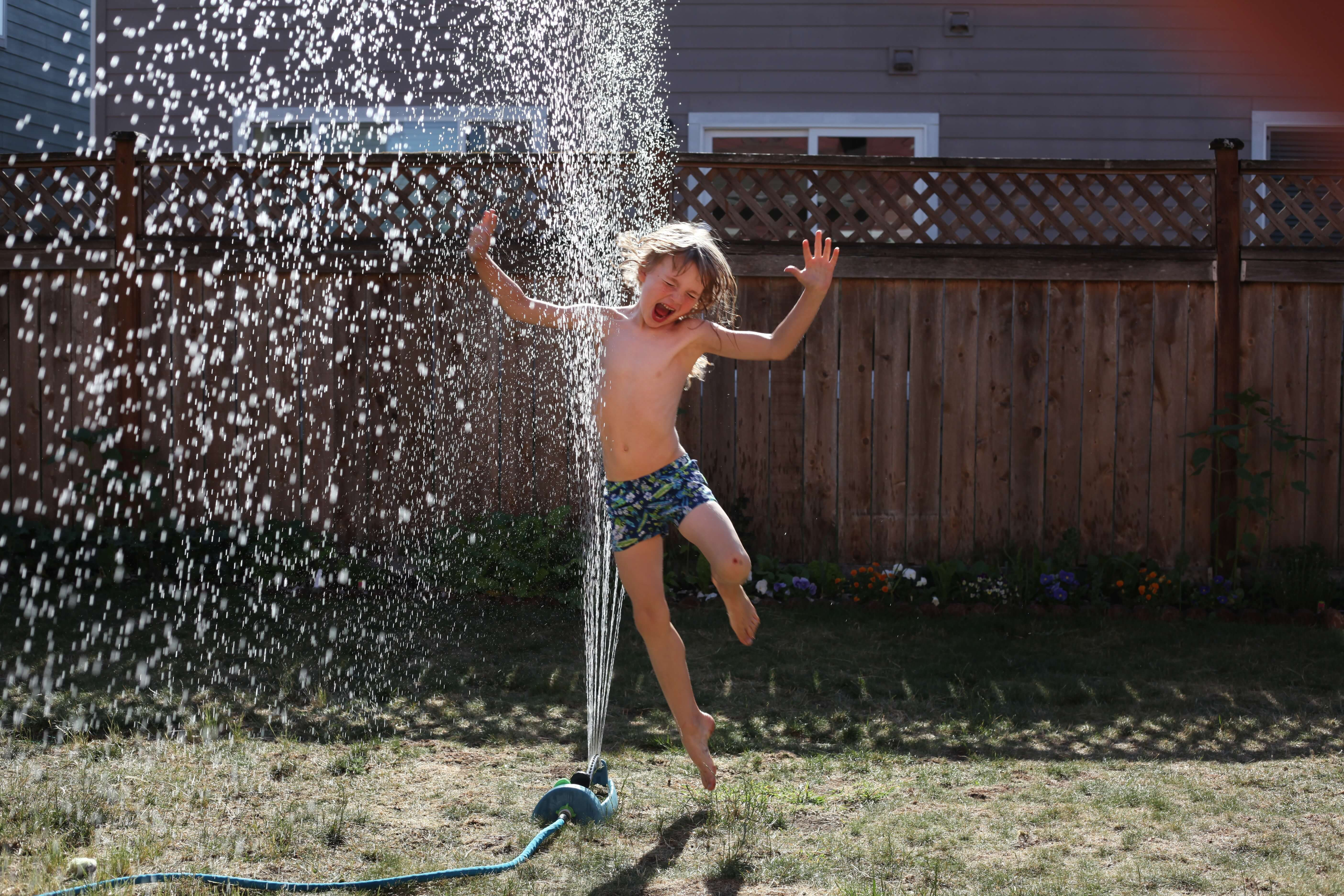 boy playing in the sprinkler, activities for last days of summer